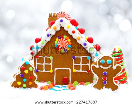 Christmas gingerbread house with twinkling silver light background - stock photo