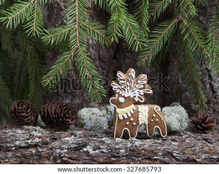 Christmas gingerbread in the form of a deer on a background of an old tree bark with fir cones and twigs eaten. - stock photo