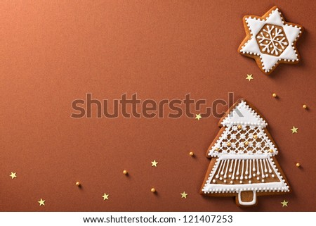 Christmas gingerbreads composition with golden stars and balls on brown paper background - stock photo