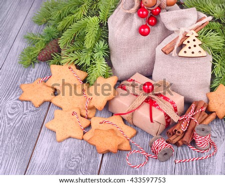 Christmas gingersnap on a string and gift sacks and a box on a wooden background. A Christmas background with space for the text. - stock photo