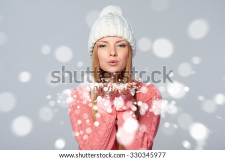 Christmas Girl. Beautiful caucasian woman wearing winter clothing hat blowing snow at you, looking at camera, over gray background - stock photo