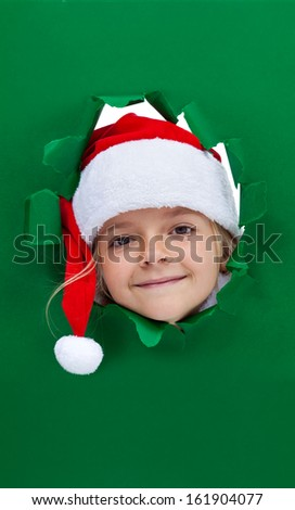 Christmas girl looking through hole in green cardboard paper - stock photo
