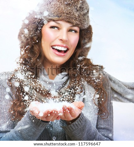 Christmas Girl.Winter woman Blowing Snow - stock photo