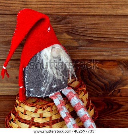 Christmas gnome, basket, brown wooden background - stock photo