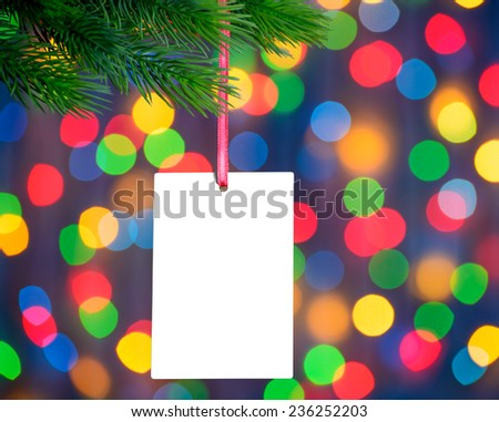 Christmas Greeting Card on the Fir Branch on the Blurred Holiday Lights Background - stock photo