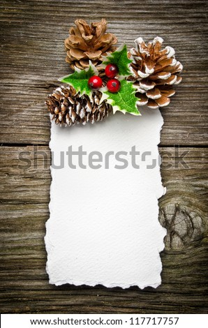 Christmas greeting card on wooden top, with holly and pine cone - stock photo