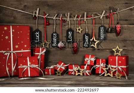 Christmas greeting card with text for love, luck and happiness. Red decoration with gifts. - stock photo