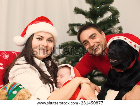 Christmas happy family of young parents, newborn baby and dog labrador - stock photo