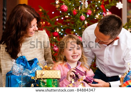 Christmas - happy family (parents with daughter) with gifts on Xmas Eve - stock photo