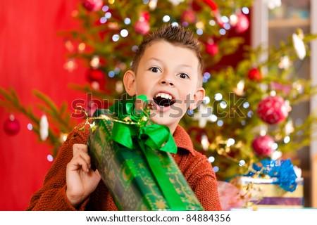 Christmas - happy little boy with Xmas present on Christmas Eve - stock photo