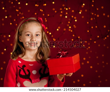 Christmas - happy smiling six years old blond caucasian child girl holding present on dark red background with lights - stock photo