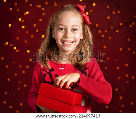 Christmas - happy smiling six years old blond caucasian child girl holding present on dark red background with lights. - stock photo