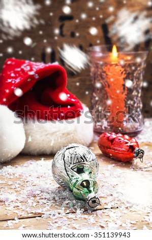 Christmas hat,candles and toys for the Christmas tree on a snowy background - stock photo
