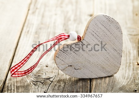 Christmas heart made of wood with rope standing on wooden background - stock photo