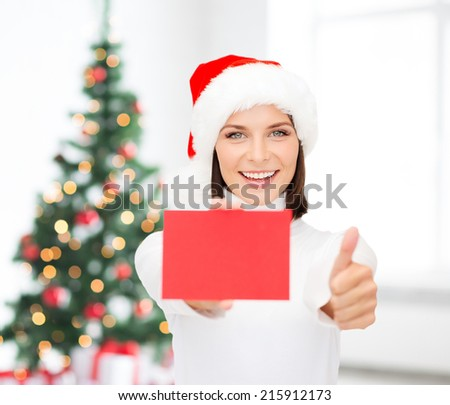 christmas, holdays, people, advertisement and sale concept - happy woman in santa helper hat with blank red card showing thumbs up gesture over living room and christmas tree background - stock photo