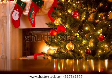 Christmas holiday background of wooden table against decorated Christmas tree and fireplace - stock photo