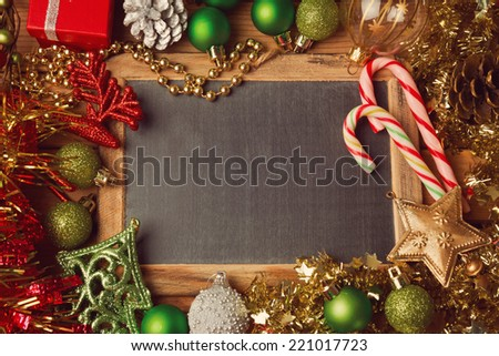 Christmas holiday background with blank chalkboard and Christmas decorations. Border design with copy space in the middle. - stock photo