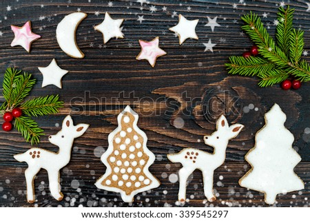 Christmas holiday background with gingerbread cookies and fir branches on the old wooden board. Drawn snowfall. Toned - stock photo