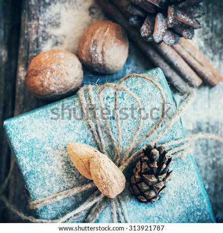 Christmas Holiday Box with Linen Cord, Decorative Snow, Almond, Natural Gifts on Wooden Background. Toned image. Vintage style - stock photo