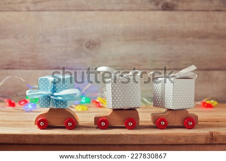 Christmas holiday concept with gift boxes on toy cars - stock photo