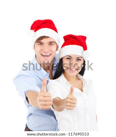 christmas holiday couple couple love excited smiling holding thumb up gesture, beautiful young man and woman smile wear new year red cap hat, isolated over white background - stock photo