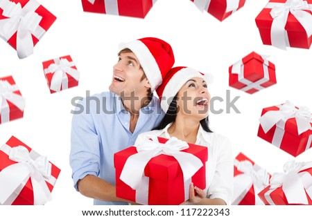 christmas holiday couple hold gift box looking up to present fall fly around, wear red new year hat cap, man and woman excited happy smile, isolated over white background - stock photo