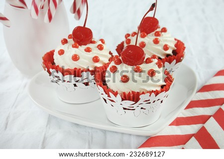 Christmas holiday dessert party food with red and white theme red velvet, cream and cherry cupcakes. Closeup. - stock photo