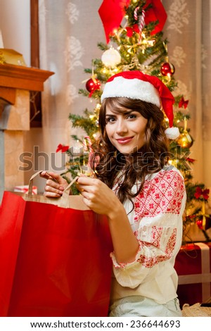 Christmas holiday happy girl after shopping, in christmas decorated living room ,wear red new year santa hat, over chimney and christmas tree colorful lights background - stock photo