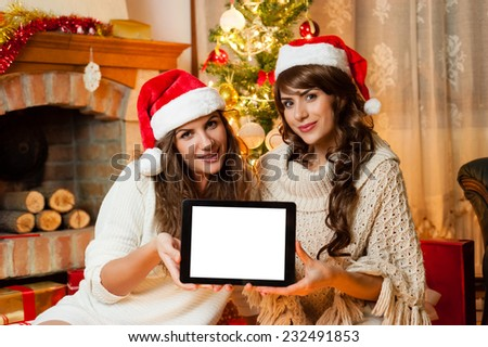 Christmas holiday happy girl friends hold tablet pad computer with space to place your text, wear red new year santa hat, over chimney and christmas tree colorful lights background - stock photo