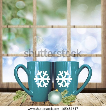 Christmas holiday mugs on wooden table over winter background. - stock photo