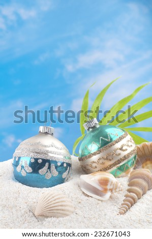 Christmas Holiday on the Beach with Two Vintage Ornaments, Sea Shells and palm frond. White sand and blue sky with clouds as background with room or space for copy, text, words.  Vertical - stock photo