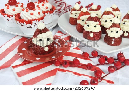 Christmas holiday Strawberry Santas with cherry red velvet cupcakes dessert party food in modern red and white theme - closeup. - stock photo