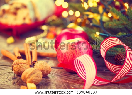 Christmas holiday table setting, decorated with garlands, baubles, walnuts, hazelnuts, cinnamon sticks. Warm colors toned. Traditional Xmas sweets food. Vintage style toned image. x-mass  - stock photo