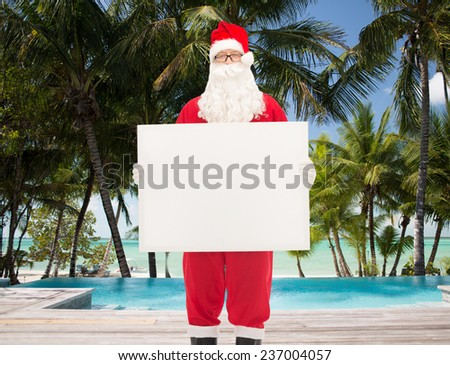 christmas, holidays, advertisement, travel and people concept - man in costume of santa claus holding white blank billboard over swimming pool on tropical beach background - stock photo
