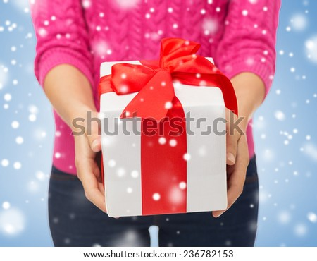 christmas, holidays and people concept - close up of woman in pink sweater holding gift box over blue background with snow over blue background with snow - stock photo