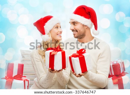 christmas, holidays and people concept - happy couple in santa hats exchanging gifts over blue holidays lights background - stock photo