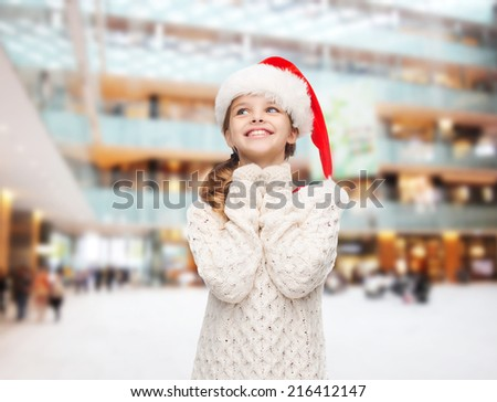 christmas, holidays, childhood and people concept - smiling girl in santa helper hat over shopping center background - stock photo