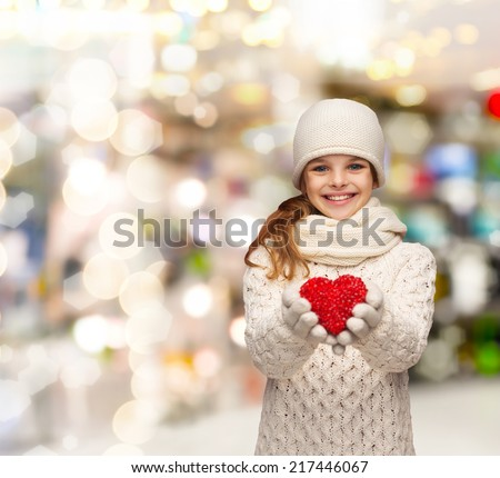 christmas, holidays, childhood, presents and people concept - dreaming girl in winter clothes with red heart over lights background - stock photo