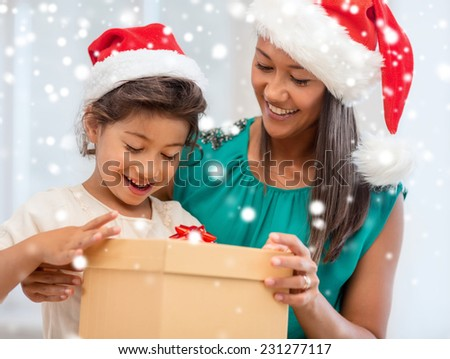 christmas, holidays, family and people concept - happy mother and child girl with gift box at home - stock photo