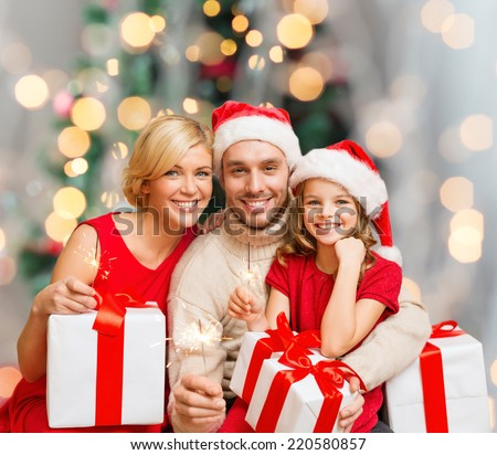 christmas, holidays,  family and people concept - happy mother, father and little girl in santa helper hats with gift boxes over living room and christmas tree background - stock photo