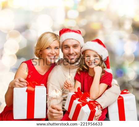 christmas, holidays, family and people concept - happy mother, father and little girl in santa helper hats with gift boxes over lights background - stock photo