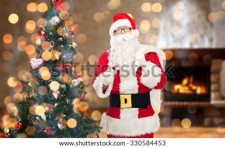 christmas, holidays, gesture and people concept - man in costume of santa claus with bag and christmas tree showing thumbs up over home fireplace and lights background - stock photo