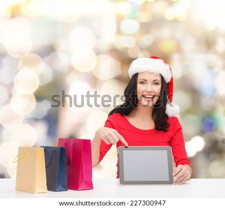 christmas, holidays, technology, advertising and people concept - smiling woman in santa helper hat with shopping bags and tablet pc computer over lights background - stock photo