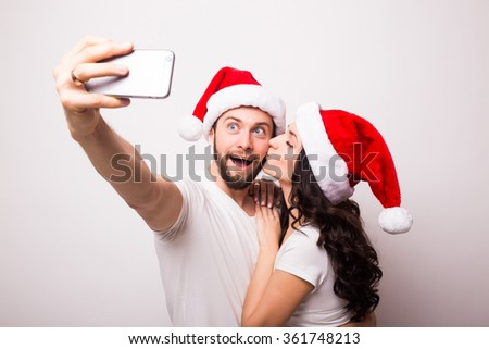 christmas, holidays, technology and people concept - happy couple in santa hats taking selfie picture with smart-phone on white background. They look at phone. - stock photo