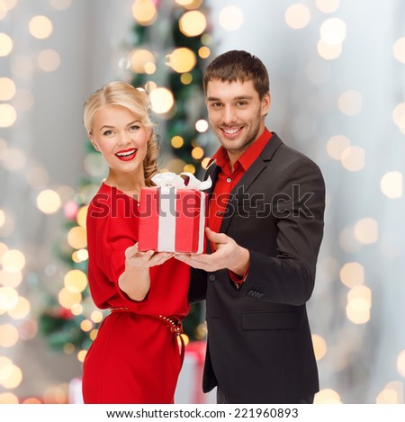christmas, holidays, valentine's day, celebration and people concept - smiling man and woman with present over living room and christmas tree background - stock photo