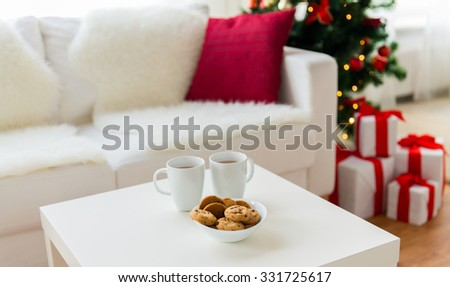 christmas, holidays, winter, celebration and still life concept - close up of cookies and cups with hot chocolate or cocoa drink on table at home - stock photo