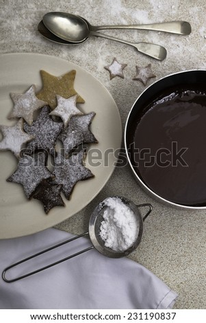 Christmas homemade cookies sprinkled by icing sugar and dish of melted chocolate - stock photo