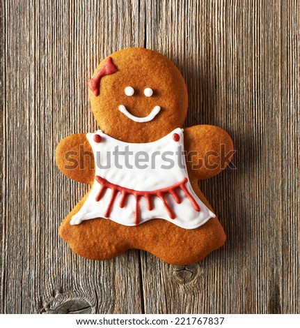 Christmas homemade gingerbread girl on wooden table - stock photo