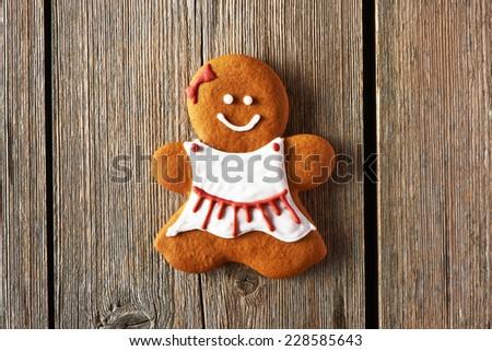 Christmas homemade gingerbread girl on wooden table - stock photo