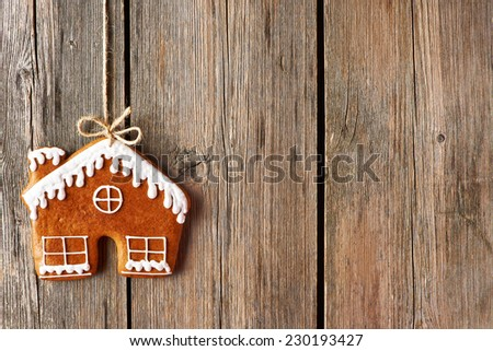 Christmas homemade gingerbread house cookie over wooden background - stock photo